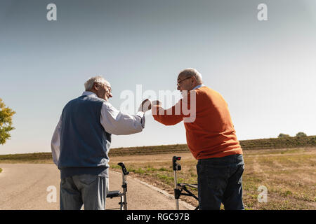 Two old friends with wheeled walkers, greeting in the street - Stock Photo