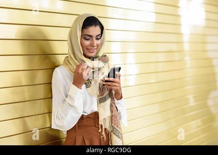 Spain, Granada, young Arab tourist woman wearing hijab, using smartphone - Stock Photo