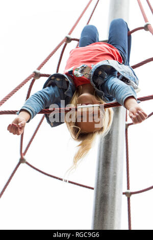 Blond girl hanging upside down on jungle gym at playground - Stock Photo