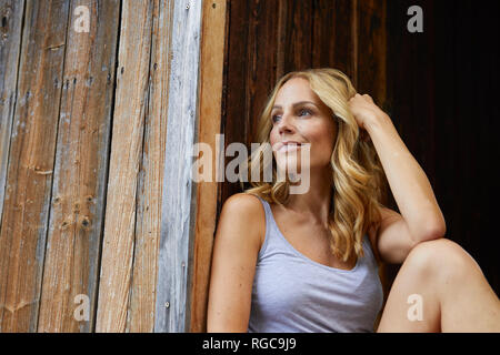 Smiling blond woman in front of wooden hut Stock Photo