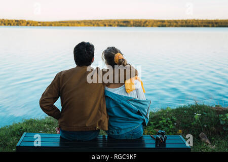 Young couple sitting on a bench, looking at the lake - Stock Photo