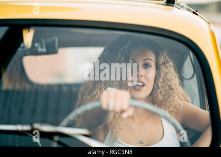 Portrait of surprised blond woman driving classic car - Stock Photo