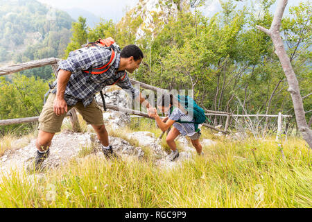 Italy, Massa, man helping a young woman to climb a step while hiking in the Alpi Apuane mountains - Stock Photo