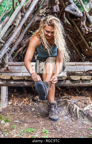 Young woman sitting on bench lacing her hiking boots - Stock Photo