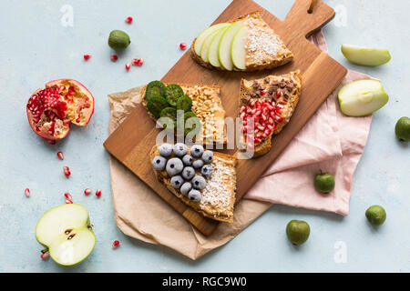 Bread slices with various toppings on wooden board - Stock Photo