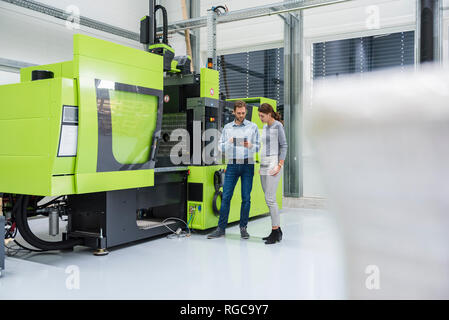 Colleagues in high tech company controlling manufacturing machines, using digital tablet - Stock Photo