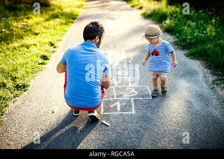 Father playing hopscotch together with his little son - Stock Photo