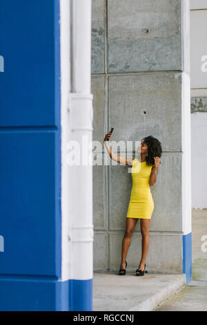 Fashionable businesswoman in yellow dress taking selfie with smartphone - Stock Photo