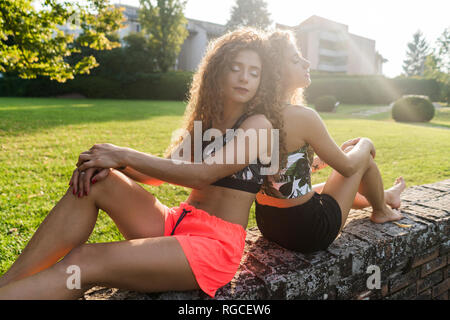 Portrait of twin sisters sitting back to back on a wall in summer relaxing - Stock Photo