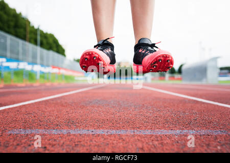 Feet of a jumping runner, mid air - Stock Photo