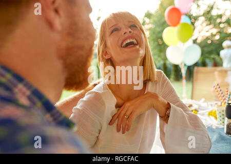 Laughing woman with man on a garden party
