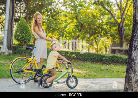 Happy family is riding bikes outdoors and smiling. Mom on a bike and son on a balancebike - Stock Photo