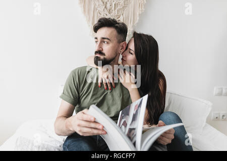 Couple sitting on bed, flipping through a book - Stock Photo