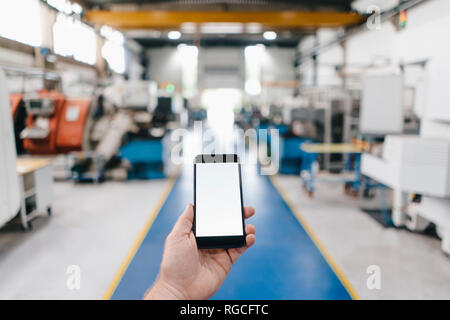 Hand holding smartphone with blank screen in a factory workshop - Stock Photo