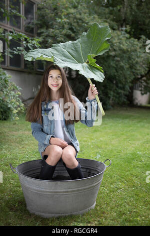 Portrait of smiling girl sitting under big in tub in in the garden - Stock Photo
