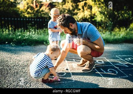 Father drawing Hopscotch on asphalt - Stock Photo