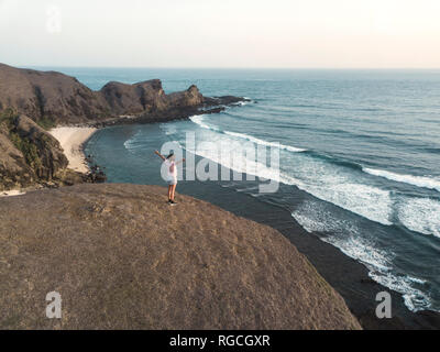 Indonesia, Lombok, young woman at coast - Stock Photo
