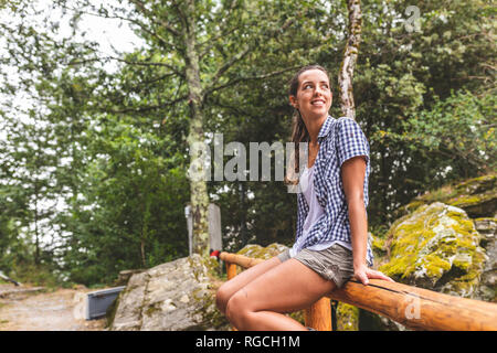 Italy, Massa, smiling young woman sitting on a wooden fence in the Alpi Apuane - Stock Photo