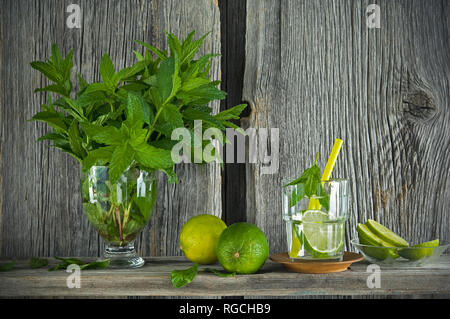 Homemade mint lemonade with lime on rustic wooden board - Stock Photo