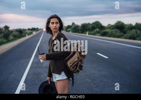 Portrait of young hitchhiking woman with backpack and beverage standing on lane - Stock Photo