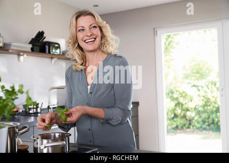 Smiling woman cooking in kitchen putting basil into cooking pot - Stock Photo