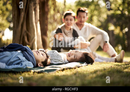 two asian children little boy and girl having fun lying on grass with parents sitting watching in background. - Stock Photo