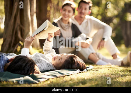 two asian children little boy and girl having fun lying on grass with parents sitting watching in background, focus on the children in foreground. - Stock Photo