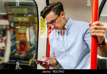 UK, London, businessman in underground train looking at cell phone - Stock Photo