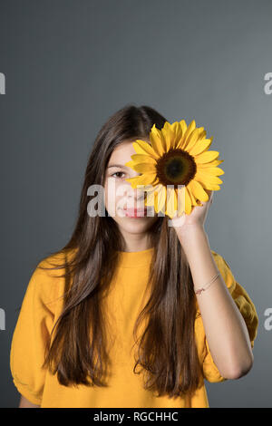 Portrait of smiling girl with sunflower in front of grey background - Stock Photo
