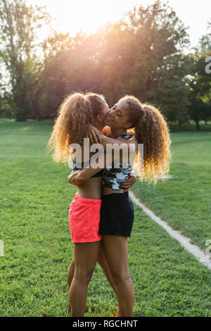 Twin sisters hugging each other in a park - Stock Photo