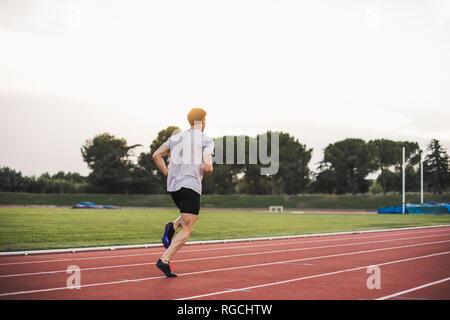 Athlete running on tartan track - Stock Photo