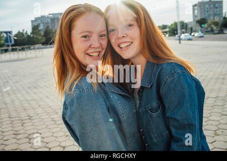 Redhead twins hugging can