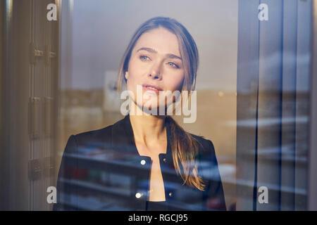 Portrait of businesswoman behind windowpane - Stock Photo