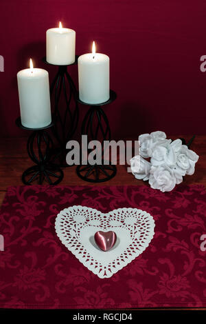 Heart shapped dollie and gemstone, three white candles in metal holoders and bouquet of white roses on wooden table. - Stock Photo