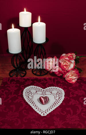 Heart shapped dollie and gemstone, three white candles in metal holoders and bouquet of orange and white roses on wooden table. - Stock Photo