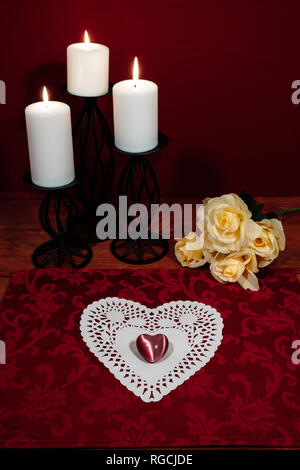 Heart shapped dollie and gemstone, three white candles in metal holoders and bouquet of yellow roses on wooden table. - Stock Photo