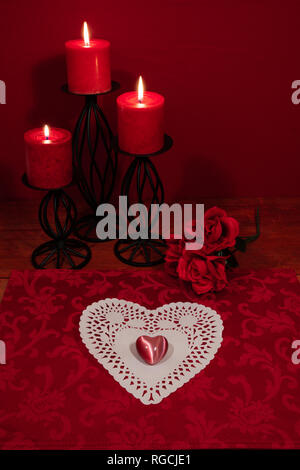Heart shapped dollie and gemstone, three red candles in metal holoders and bouquet of red roses on wooden table. - Stock Photo