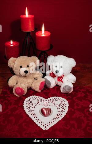Heart shapped dollie and gemstone, three red candles in metal holders and red rose, two teddy bears on wooden table. - Stock Photo