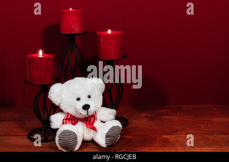 Three red candles in metal holders and red rose, one teddy bear on wooden table. - Stock Photo