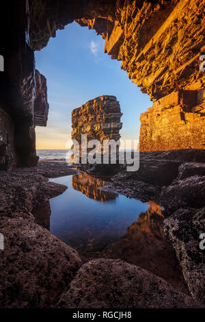 Dun Briste sea stack framed by a cave beneath Downpatrick Head. County Mayo, Ireland. - Stock Photo