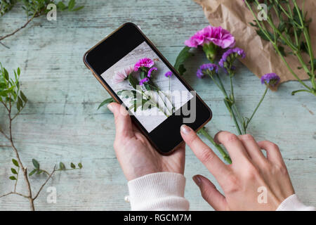 Woman's hands taking photo of flowers with smartphone - Stock Photo