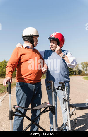 Two old friends wearing safety helmets, preparing for a wheeled walker race - Stock Photo