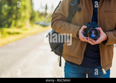 Finland, Lapland, close-up of man holding camera on country road - Stock Photo