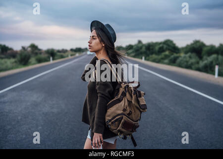Portrait of hitchhiking young woman with backpack and beverage on lane - Stock Photo