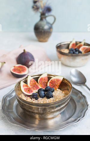 Bowl of porridge with sliced figs, blueberries and dried berries