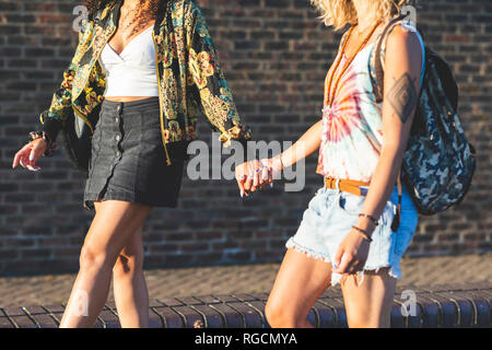 Two young women holding hands walking along brick wall - Stock Photo