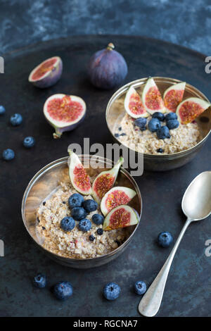 Bowls of porridge with sliced figs, blueberries and dried berries - Stock Photo
