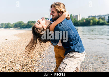 Happy young couple in love embracing at the riverside