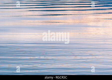 Gentle ripples on surface of lake reflecting pink, purple, and blue colors in sky at sunset - Stock Photo