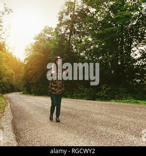 Woman traveler with backpack walking along the road. Travel and backpacking lifestyle concept - Stock Photo